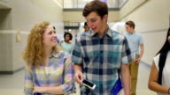 Teenage high school students smiling while walking together in busy hallway video