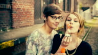 Teenage hipster couple cheerfully making soap bubbles video