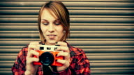 Teenage hipster woman having fun taking pictures with old camera video