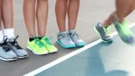 Teenage legs wearing athletic shoes in a line, walking away video