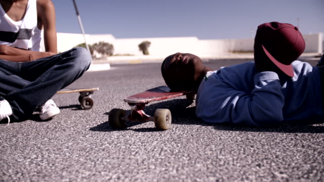 Teenage longboarder sitting and lying on their longboards video