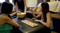 Teenage sisters playing board game at home, mom serving popcorn video