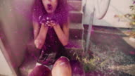 Teenaged hipster girl sitting on a pavement blowing pink glitter video