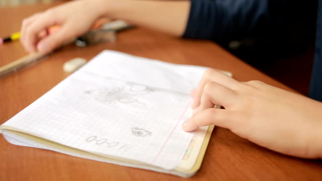 A teenager draws a simple pencil in a notebook. Close-up video
