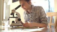 Teenager girl doing lab works with microscope video