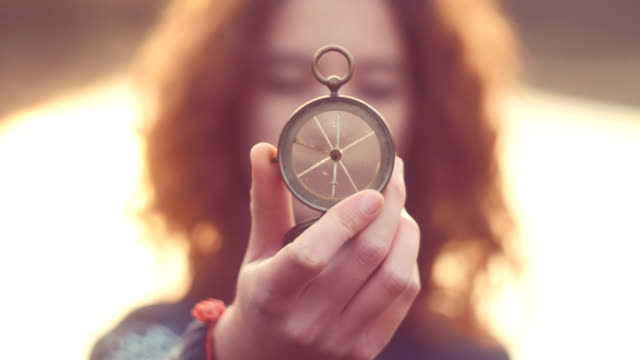 Teenager girl  holding an old compass in hand video