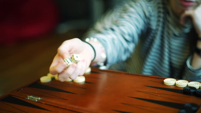 Teenager girl play backgammon, throwing dice video