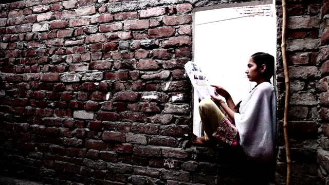 Teenager girl reading a book at home video