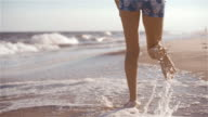 Teenager girl running on the beach, long plane include the legs and footprints closeup video