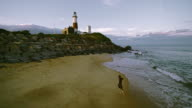 Teenager girl walking and running in front of Montauk Lighthouse. Drone aerial footage. video