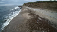 Teenager girl walking away on the ocean shore at Montauk Point. Aerial footage video
