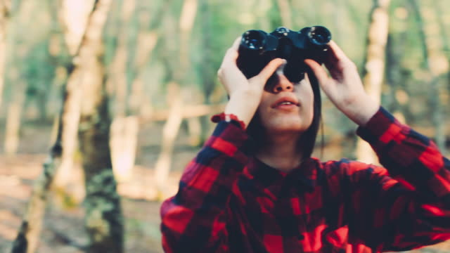 Teenager girl with binoculars in the forest video