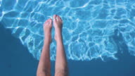 Teenager girl's legs in the water of the backyard's pool video