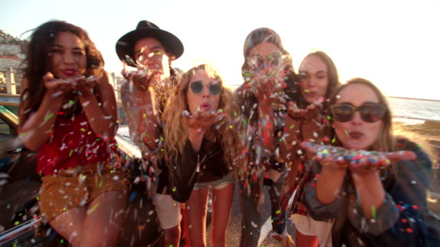 Teenager hipster friends celebrating by blowing colorful confetti from hands video