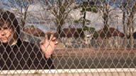 Teenager / Hoody staring through wire fence video