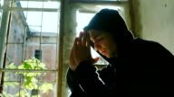 Teenager in the hood sits on a window sill, holding his hands in his head to pray. In the rays of the sun video
