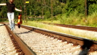 A teenager male walks along the railway with a guitar in his hands video