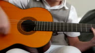 Teenager playing guitar (closeup) video