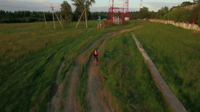 Teenager riding bike in the country, aerial view video