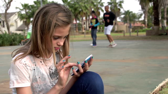 Teenager texting on cell phone in park while others playing soccer video