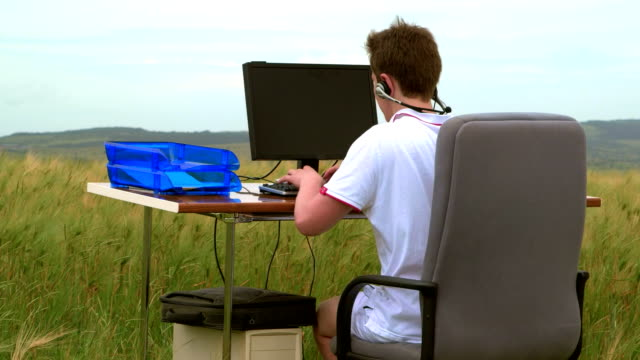 Teenager using desktop computer outdoors video