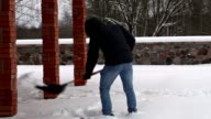 Teenager using snow shovel in winter video