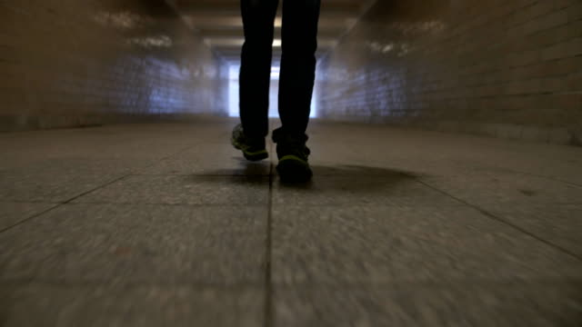 Teenager walking on a narrow tunnel, feet close-up video