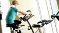 Teenager working out on the exercise bike at the gym video
