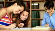 Teenagers learning together indoors in library video
