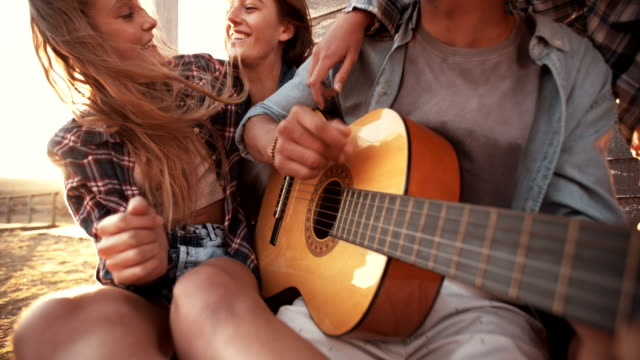 Teenagers listening to guy playing his guitar video