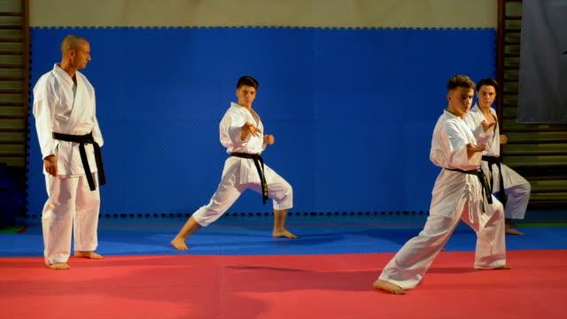 Teenagers martial arts practitioners performing kata at the dojo with sensei karate teacher video