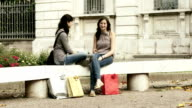 Teenagers talking on a bench after shopping video