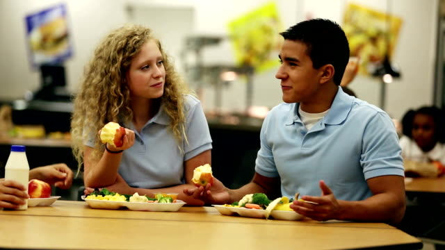 Teenagers talking over lunch in school cafeteria video