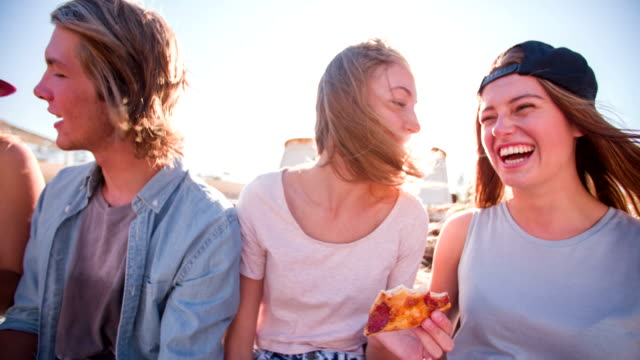 Teens eating pizza outdoors with sun flare video