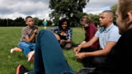 Teens hanging out in park video