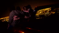 Teens hugging on a convertible looking at night city lights video