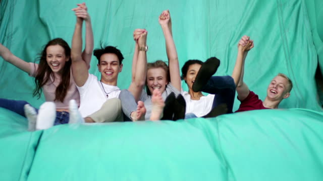 Teens Jumping Down a Slide at Fairground video