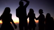 Teens looking at the ocean after sunset on a mountain video