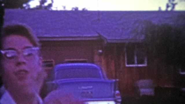 1964: Teens road trip in the family truckster rushing to leave while dad films last minute. video