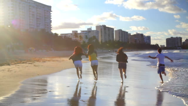 Teens run down beach together video