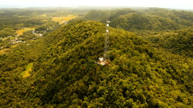 Telephone signal tower among green forest and mountains. Aerial view. Siargao island Philippines video