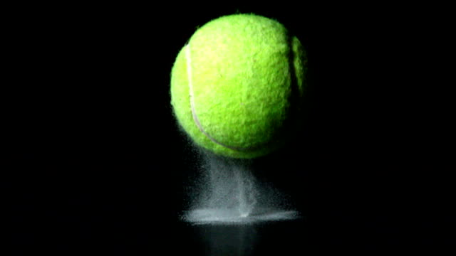 Tennis ball falling on black background video