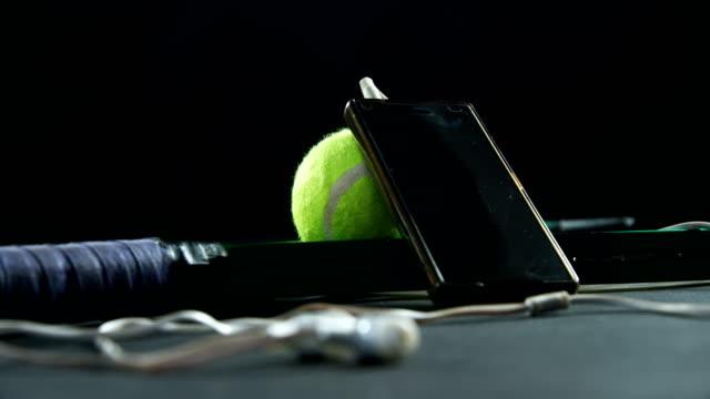 Tennis balls, racket and mobile phone with headphones in studio 4k video