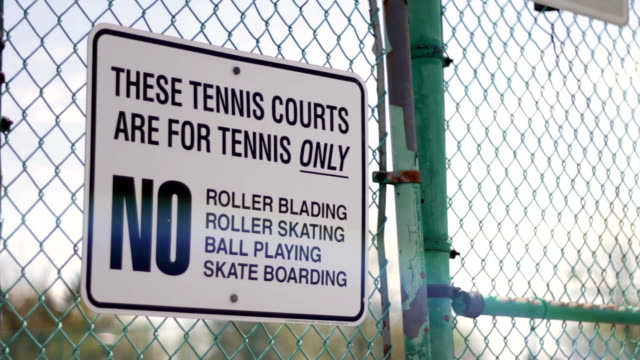 A Tennis Court Rules sign on a green fence with lens flare in daylight video