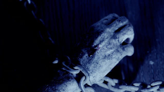 terrible burnt hand is chained to an iron chain. monster hand on Halloween video