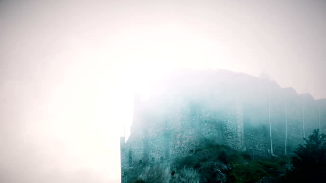 Terrible medieval building with stone walls hidden in fog. Mystical video