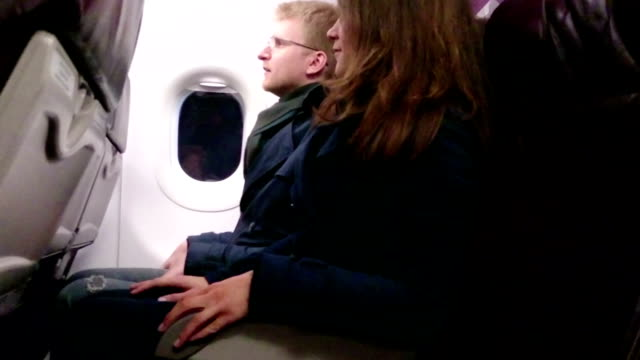 Terrified airliner passengers holding hands, hugging. Plane crashing, falling video