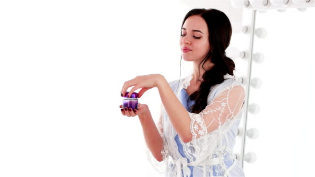 testing well-smelling daily face cream in violet jar, smiling girl holding jar of skin care product video