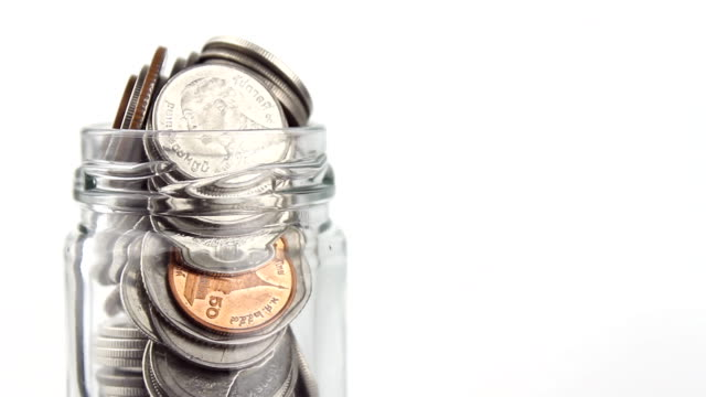 Thai Baht coin in a clear glass water rotating on a white background video