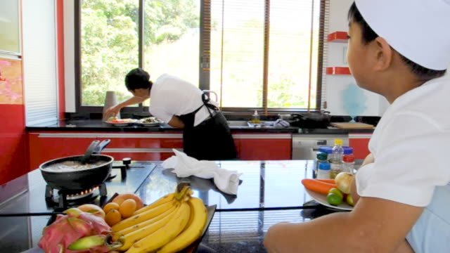 Thai man - chef - is cooking, his little son in chef's hat nearby sitting on the table in a modern style home kitchen. Making Thai food, having fun at the kitchen video